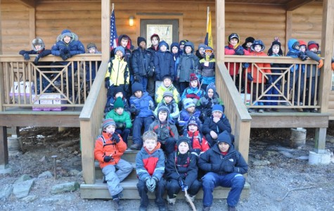 The Cub Scouts of Pelham Pack 1 in front of cabin during winter campout.