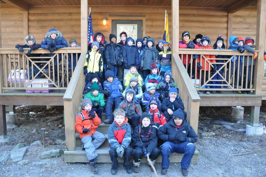 The+Cub+Scouts+of+Pelham+Pack+1+in+front+of+cabin+during+winter+campout.